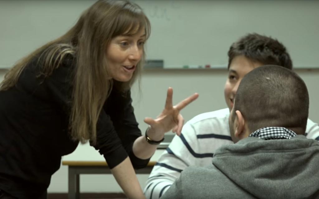 En lærer snakker med to elever i klasserommet.