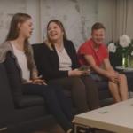 Tre ungsommer sitter i en sofa og ler og snakker sammen.