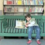 En gutt sitter og leser i en grønn sofa.