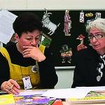 To kvinner sitter ved et bord og ser på noen papirer.