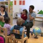 En far med et barn på fanget sitter foran en gruppe barn og gjør bevegelser til sang.