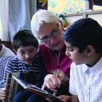 En dame sitter og leser i en bok sammen med to barn.