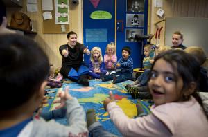 Barn som sitter i en ring. Det ser ut som de synger mens de har tomlene opp.