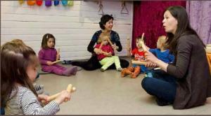 Barn og voksne sitter i en ring og spiller på instrumenter. Foto