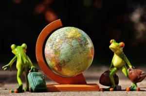 en globus og to frosker i modellleire som går rundt den, bærende på hver sin koffert