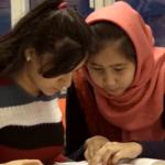 Bilde av to elever som ser på en tekst sammen