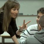 Bilde av en lærer som holder opp tre fingre og snakker med to elever