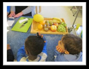 barn sitter ved et bord der det ligger frukt og en skjærefjøl.