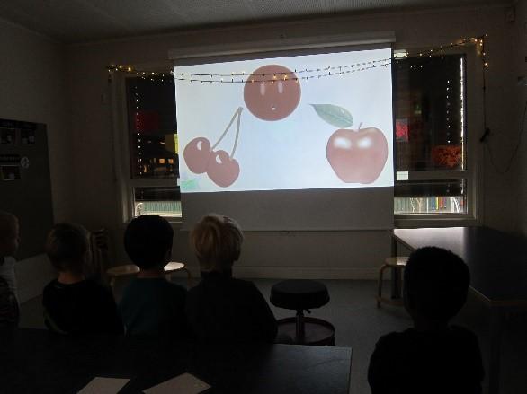 barn ser på en storskjerm med bilde av kirsebær og eple
