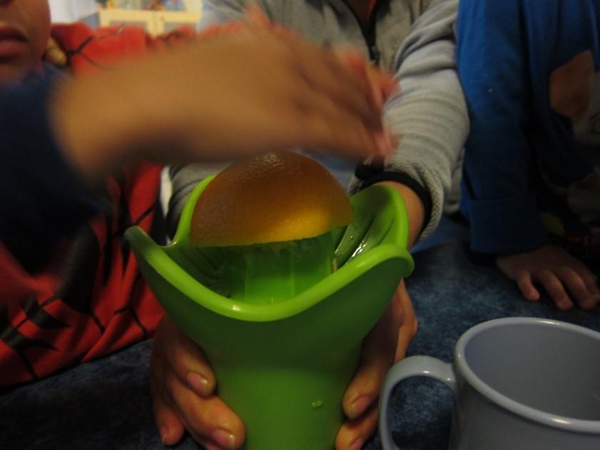 barnehender presser en appelsin i en appelsinpresse