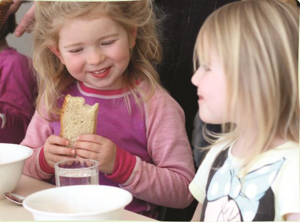 to barn sitter og spiser ved et bord. Ei jente holder et knekkebrød.