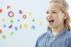 Illustrasjonsbilde av jente med bokstaver som kommer ut av munnen