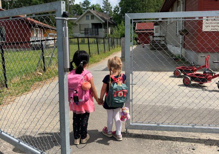 to barn går hånd i hånd inn porten til en barnehage