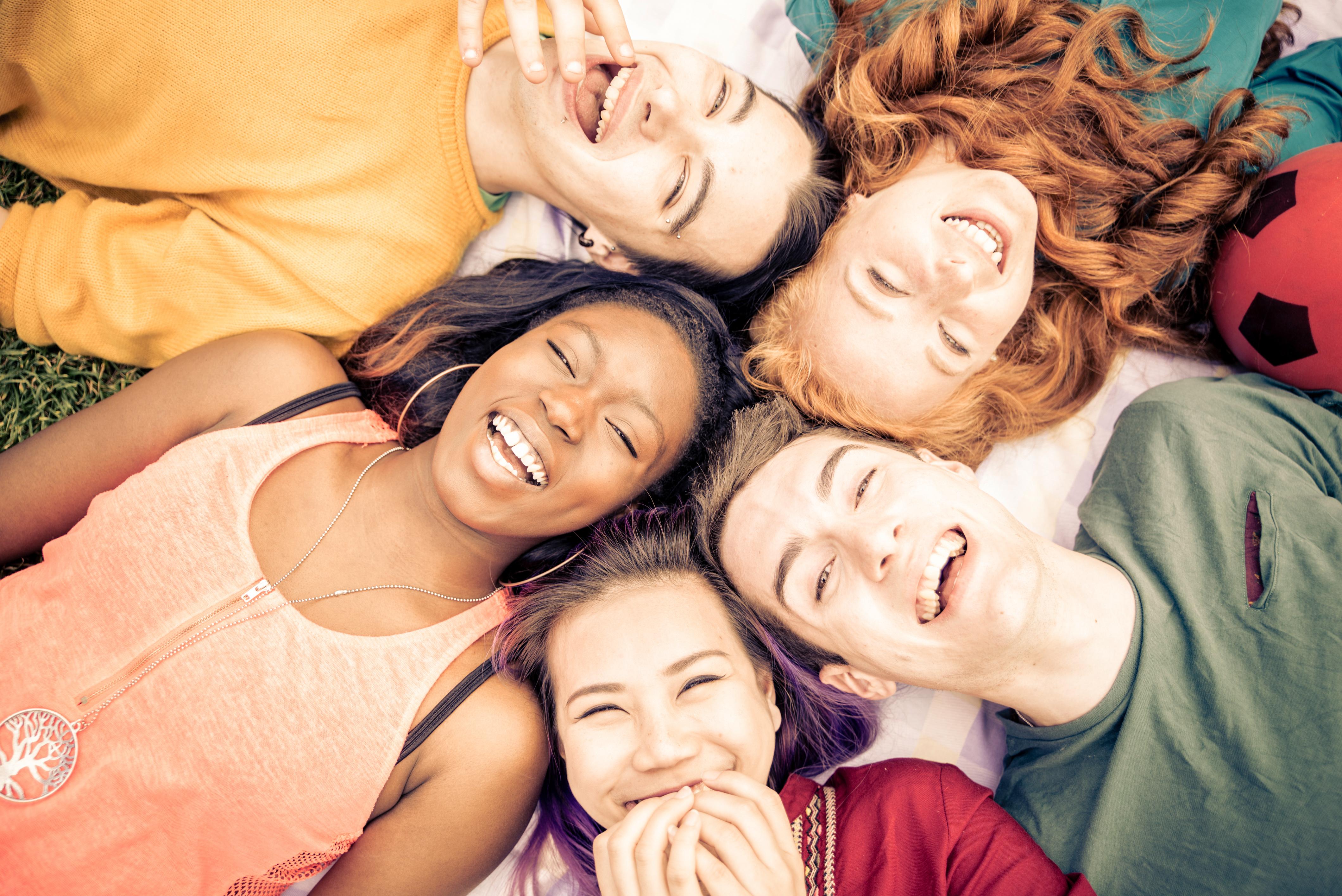 Fem ungdommer ligger på bakken og ler. Foto.