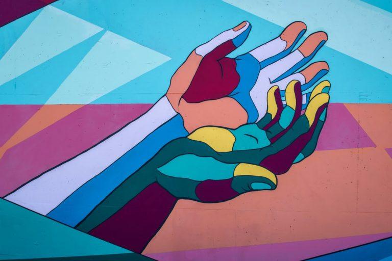 Veggmaleri med to fargerike hender