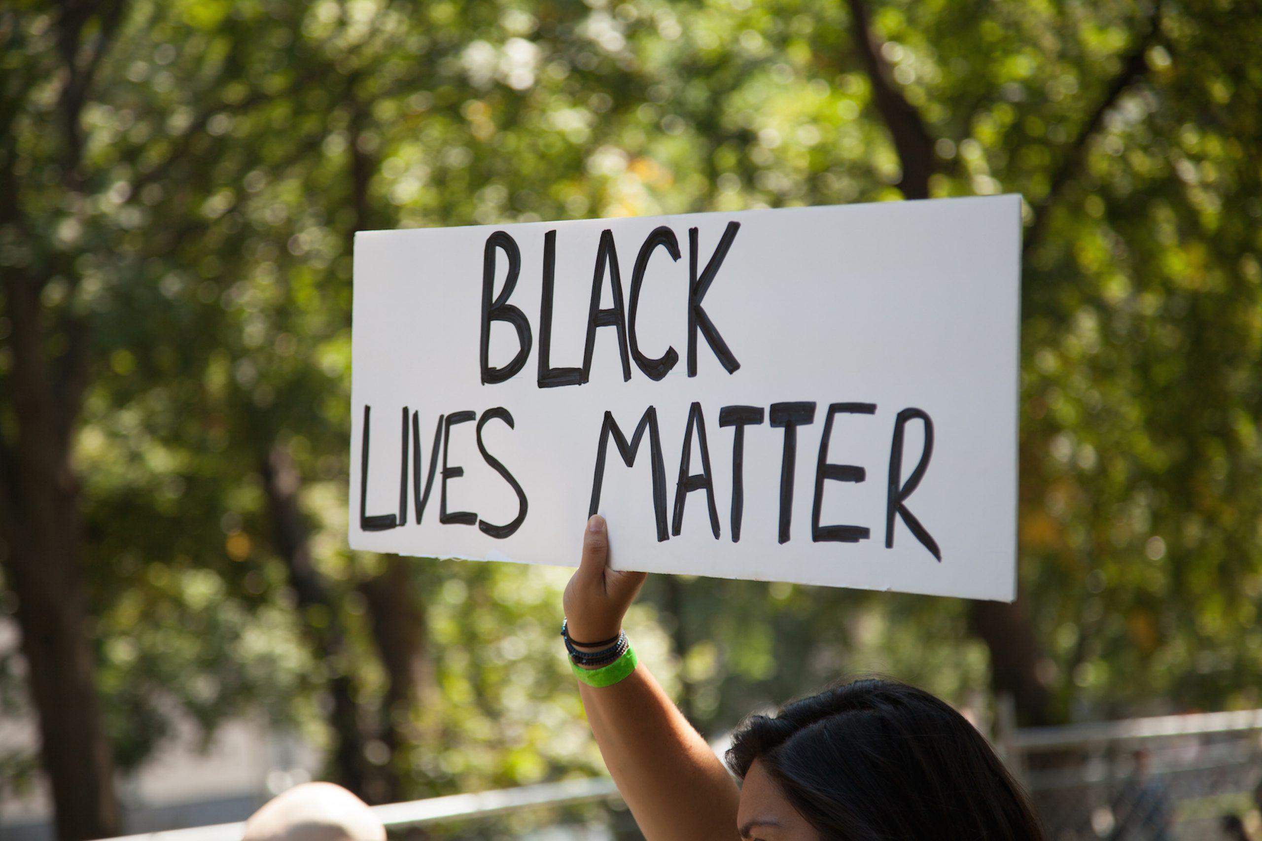 """Kvinne holder opp skilt med teksten """"Black Lives Matter"""""""