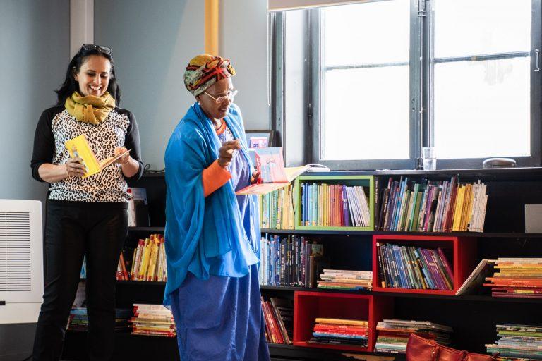 to damer står og leser høyt fra en bok