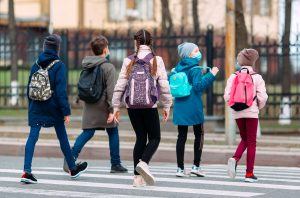 skoleelever med munnbind krysser veien. Sett bakfra.