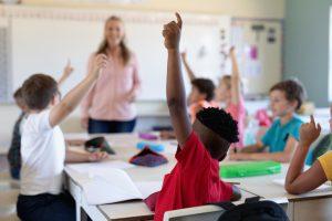 Elever rekker opp hendene i et klasserom. Læreren står ved tavla.