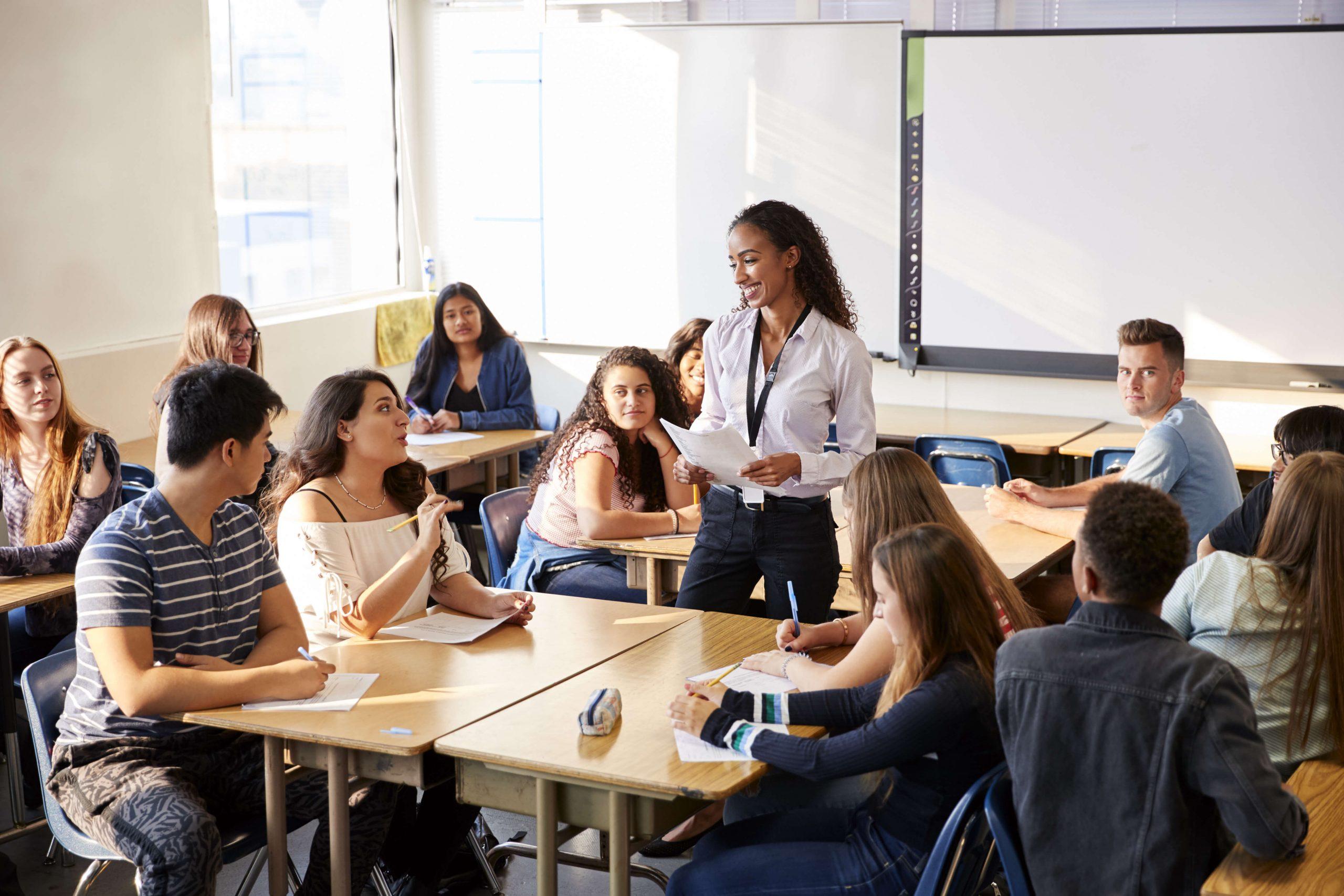 Kvinnelig lærer med elever/deltakere i et klasserom.