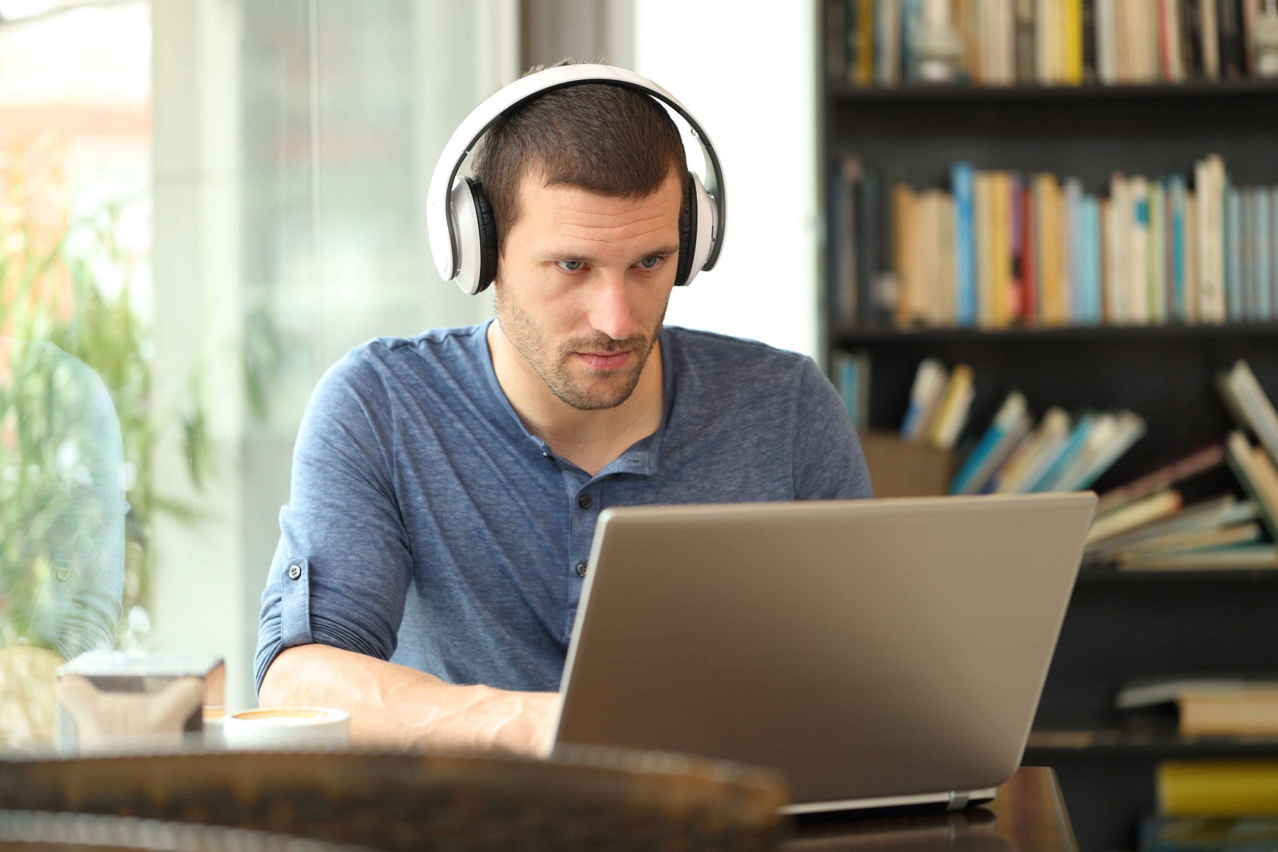 mann med headset sitter foran laptop og studerer