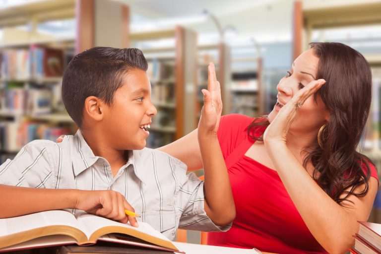 en elev og en lærer smiler og gir hverandre high five