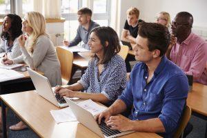 Voksne studenter sitter i et klasserom.