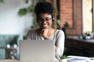 kvnne med hodetelefoner ser på en laptop og smiler