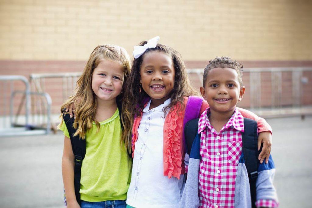 Tre barn poserer i skolegården