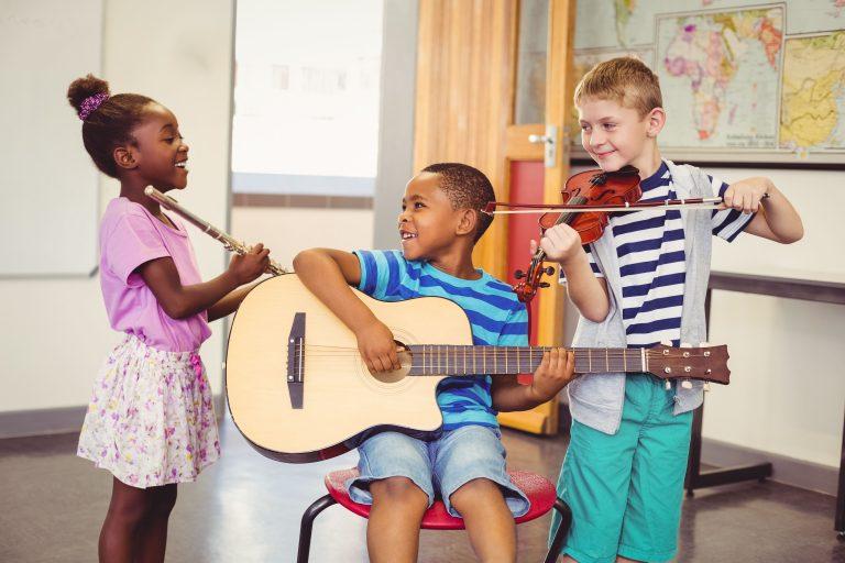 tre barn synger og spiller gitar.