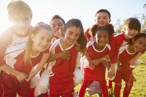 En gjeng barn i røde trøyer på fotballbanen.