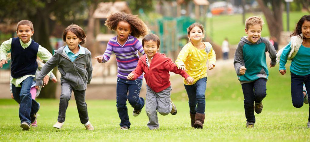 En rekke barn løper på gresset.