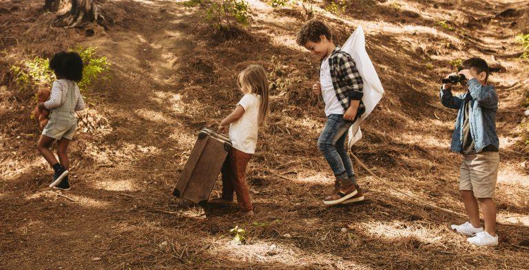 Fire barn med ulik hudfarge leker sammen ute i skogen.