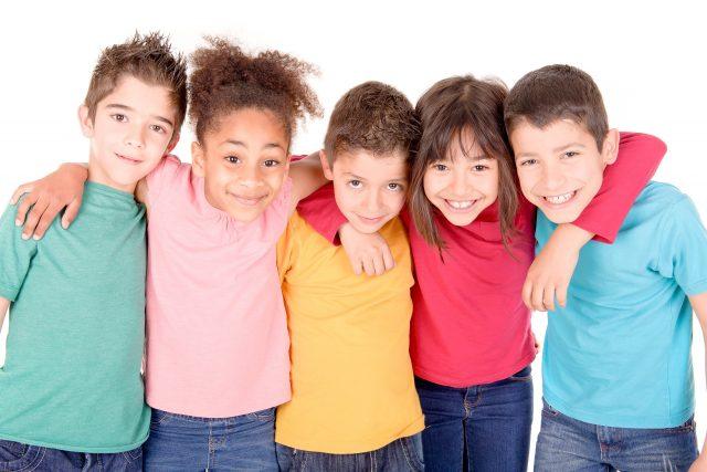 Fem barn med ulik hudfarge står på rekke og holder rundt hverandre.