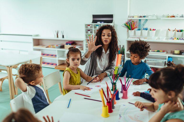 En lærer og noen barn sitter rundt et bord og arbeider med formingsaktiviteter.