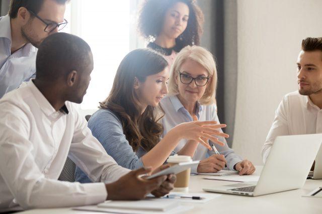 6 lærere sitter rund en skjerm og diskuterer noe.