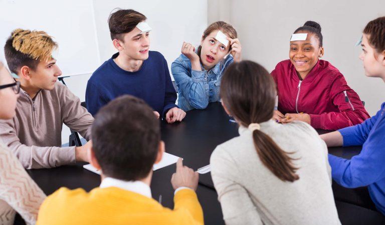 En gruppe ungdommer spiller et spill sammen. I panna har de hvite lapper.