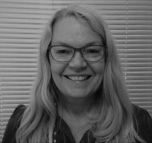 Portrettfoto av Marianne Grødum_kvinne med langt lyst hår og briller