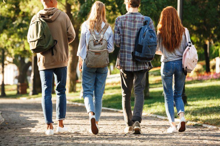fire ungdommer sett bakfra når de går ute