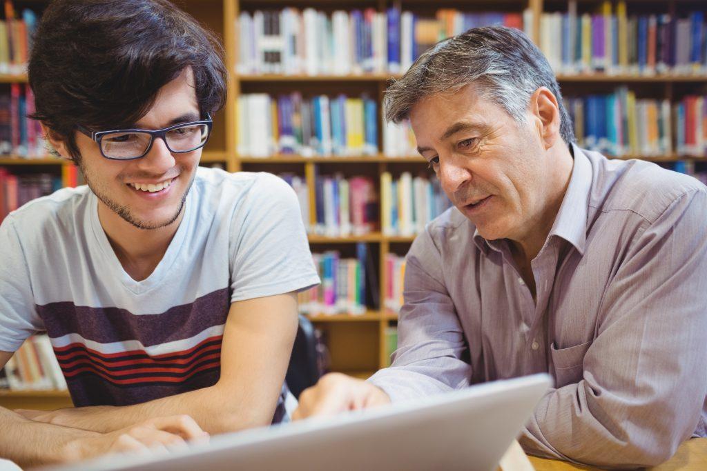 en ung og en godt voksen mann sitter og ser på en dataskjerm